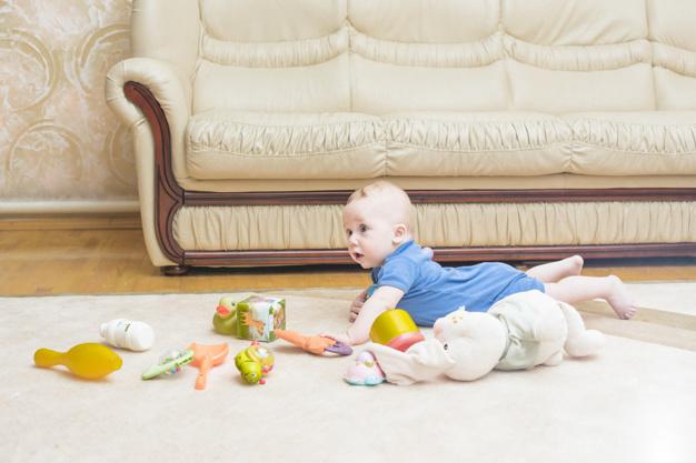 Μωρό επάνω σε χαλί με λούτρινα παιχνίδια
